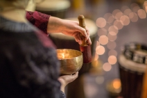 Woman playing on a tibetian singing bowl (shallow DOF; color ton